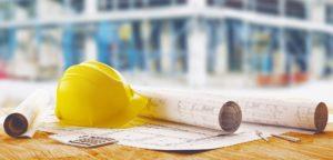 Baupläne für den Hausbau und Bauhelm liegen auf einem Tisch