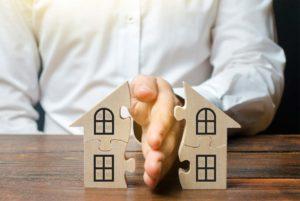 Hand teilt ein Haus in zwei Hälften, als Symbol für den Verkauf einer Immobilie bei Scheidung