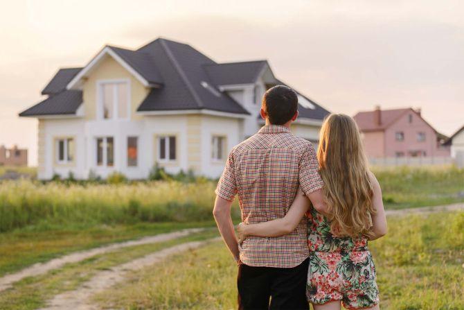 Paar steht im Sonnenuntergang vor einem Haus