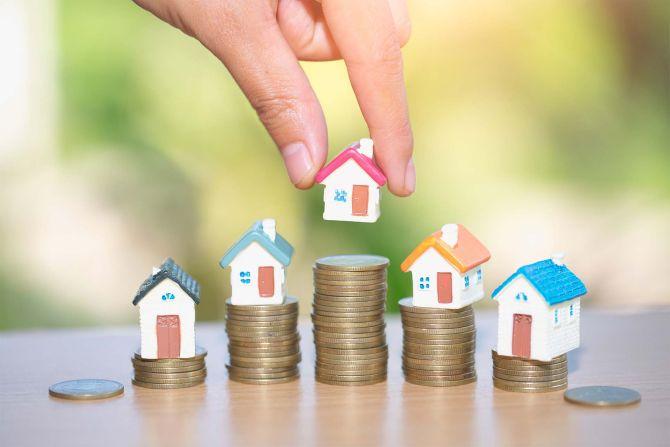 Eine Person setzt kleine Häuser auf Stapel aus Münzen